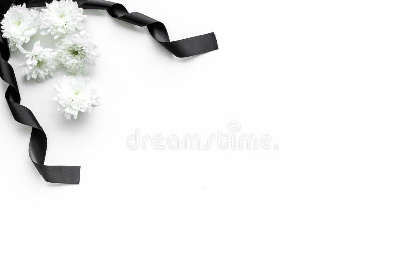 Begravnings- symboler Vit blomma nära svart band på vitt utrymme för kopia för bästa sikt för bakgrund royaltyfri fotografi