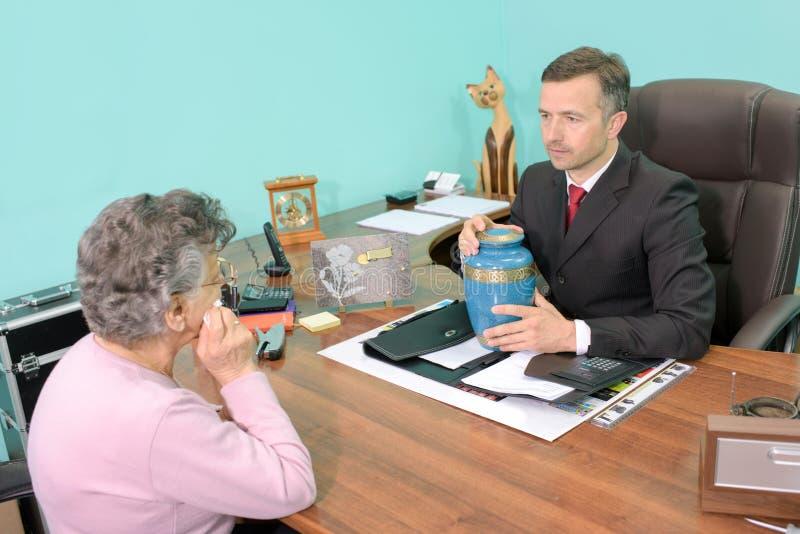 Begravningsentreprenör i möte med den hållande urnan för kvinna fotografering för bildbyråer