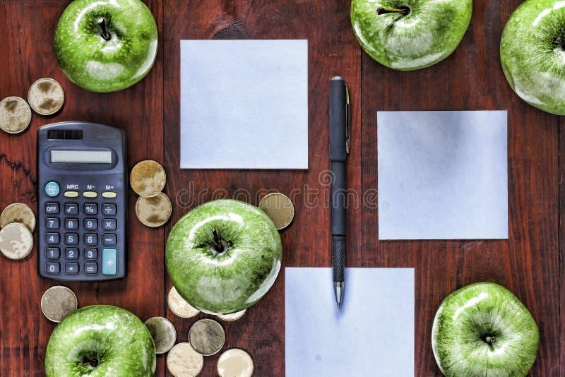 Begrepp: affär investering, anrikning, logistik som planerar Gröna äpplen, guld- mynt, räknemaskin och papper för tillträden på royaltyfri foto