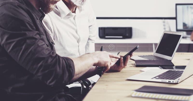 Begrepp av affärsfolk som möter process Skäggig hållande mobiltelefon för ung man och rörande skärm Vuxen affärsman arkivfoton