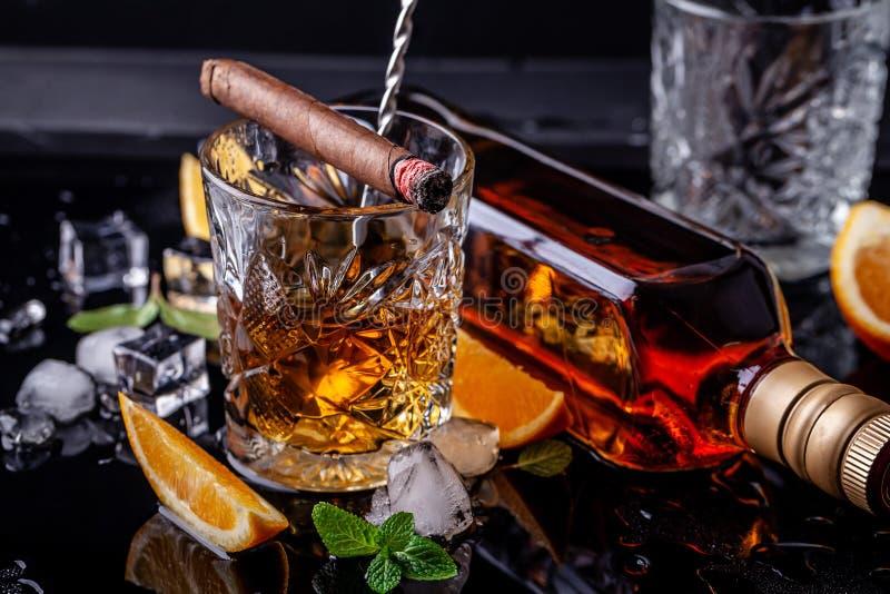 Begrepp av alkoholism, ensamhet, beroende En flaska av whisky, ett exponeringsglas av whisky och med is, en cigarr med rök på en  royaltyfri foto
