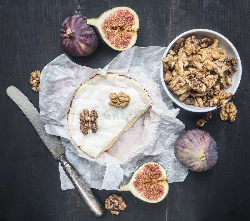 Begrepp av aptitretare för vin, camembertost, mörka druvor, valnötter och fikonträd på trälantlig bakgrund arkivfoton