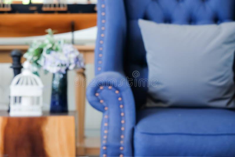 Begrepp av att göra suddig: Hemmiljögarnering med amerikanNewport stil, vardagsrum har en blå soffa och en trätabell arkivbilder