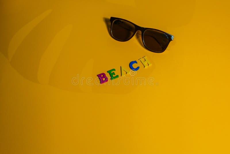 Begrepp av att koppla av i skuggan på stranden inskriftstrand i skuggan av en bladmonstera på en gul bakgrund royaltyfria foton