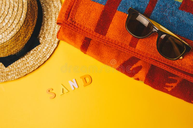 Begrepp av att koppla av på stranden inskriftsand på en gul bakgrund med solglasögon, en handduk och en sugrörhatt Top besk?dar arkivfoto