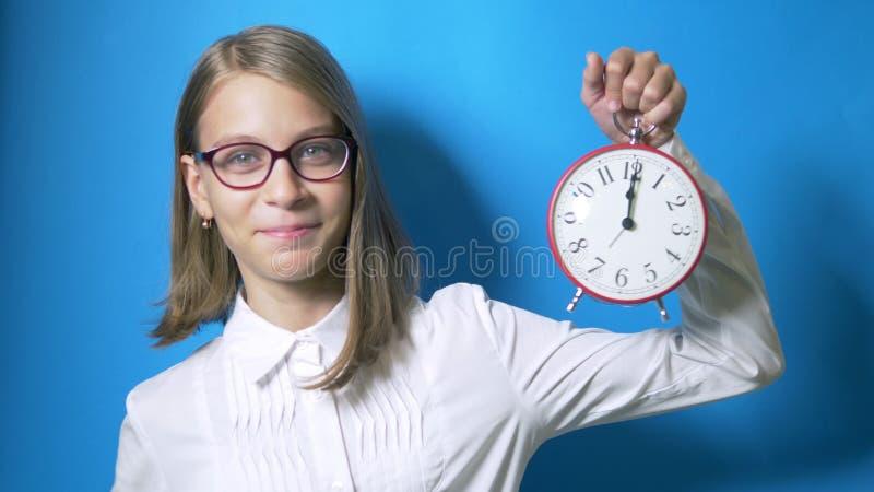 Begrepp av att studera tid, tillbaka till skola En smart flickaskolflicka med exponeringsglas rymmer en stor klocka och visar ett arkivfoto