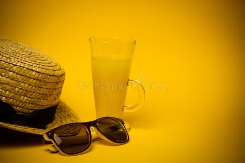 Begrepp av avkoppling och som törstar på stranden ett exponeringsglas av lemonad på en gul bakgrund med solglasögon och en sugrör royaltyfria foton