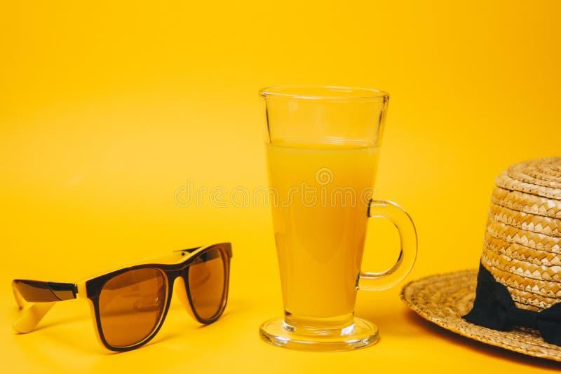 Begrepp av avkoppling och som törstar på stranden ett exponeringsglas av lemonad på en gul bakgrund med solglasögon och en sugrör royaltyfria bilder