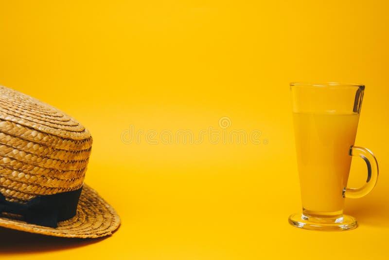 Begrepp av avkoppling och som törstar på stranden ett exponeringsglas av lemonad på en gul bakgrund med en sugrörhatt Top besk?da royaltyfri bild