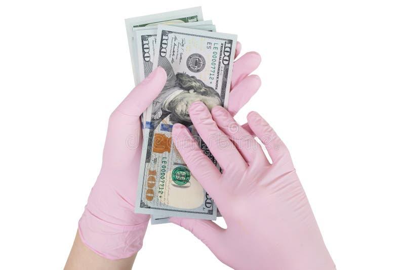 Begrepp av betald medicin behandskade händer som rymmer dollar arkivbild
