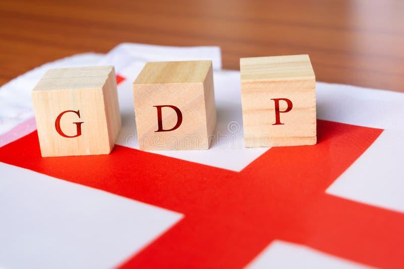 Begrepp av bruttonationalprodukten eller BNP av England, BNP i träkvarterbokstav på den England flaggan fotografering för bildbyråer