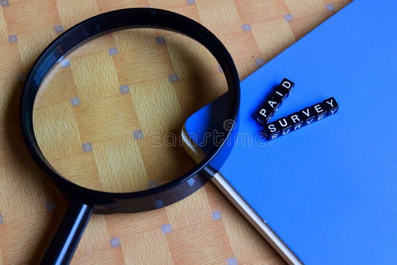 Begrepp av den betalda granskningen på träkuber med böcker i bakgrund arkivfoto