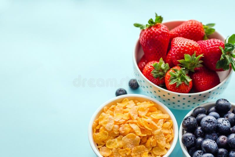 Begrepp av den fria frukosten för sund gluten med bär och havreflingor i de vita bunkarna på en blå bakgrund, tre arkivfoto