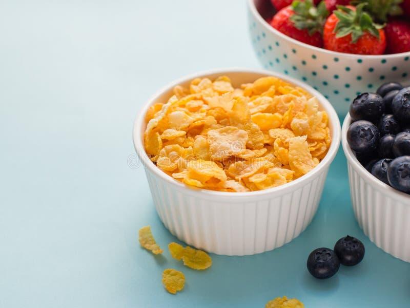 Begrepp av den fria frukosten f?r sund gluten med b?r och havreflingor i de vita bunkarna p? en bl? bakgrund, tre arkivbild