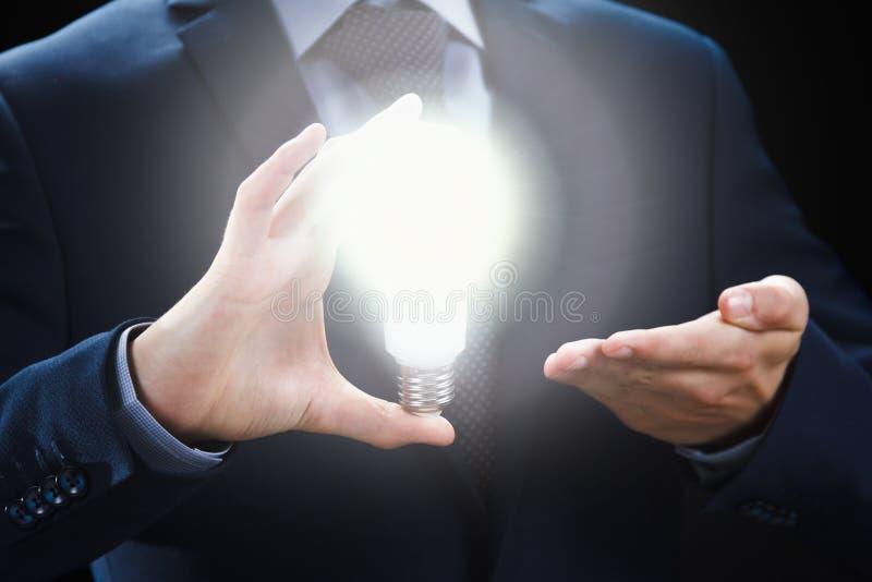 Begrepp av den idérik och inspirationidén Händer av affärsmannen som rymmer den upplysta ljusa kulan royaltyfria foton