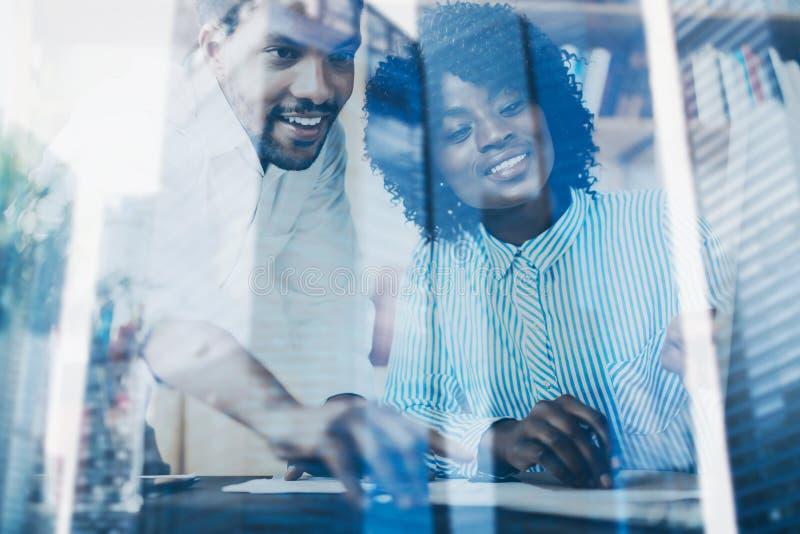 Begrepp av dubbel exponering Två unga coworkers som tillsammans arbetar i ett modernt kontor Svarta affärspartners som diskuterar royaltyfri fotografi