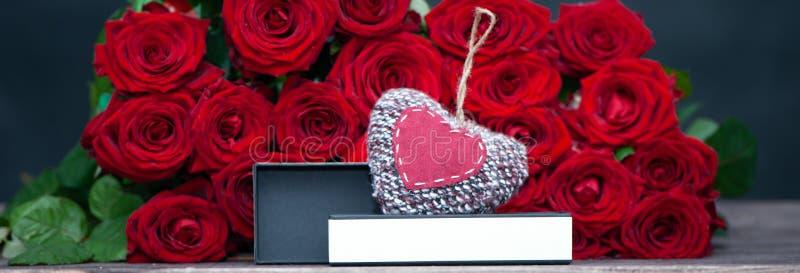 Begrepp av en gåva för valentin dag stor grupp av röda rosor och en öppen ask med ett stilfullt, arkivfoto