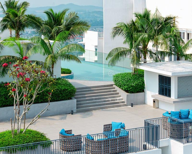 Begrepp av en ideal exotisk semester - bästa sikt av den härliga taköverkanten med simbassängen, vardagsrumzon, gröna träd arkivfoton