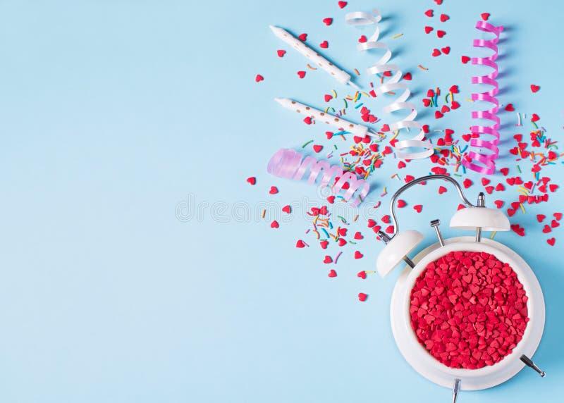 Begrepp av födelsedag-, valentin- och partitid på blå pastellfärgad bakground med larmet royaltyfri foto