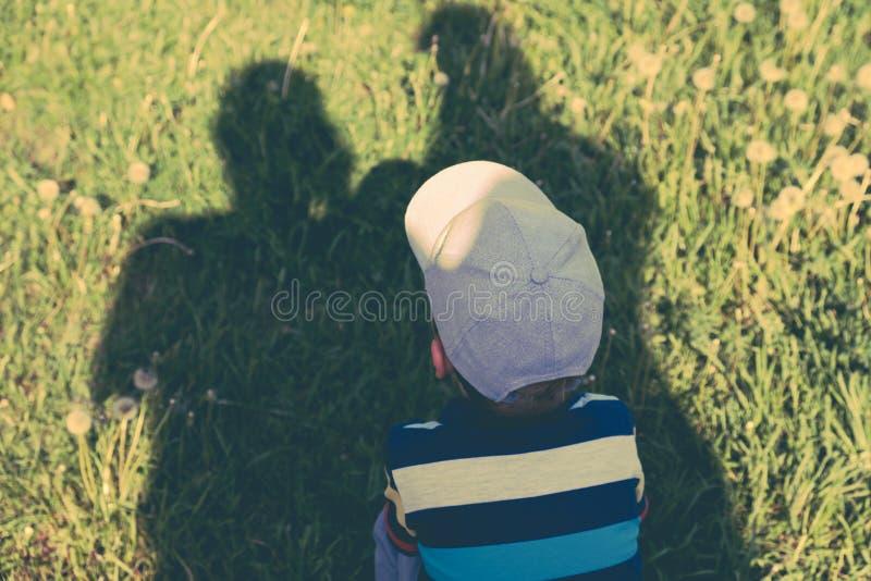 Begrepp av familjen Skuggor av föräldrar, fadern och modern skyddar barnet från den bränning solen arkivbild
