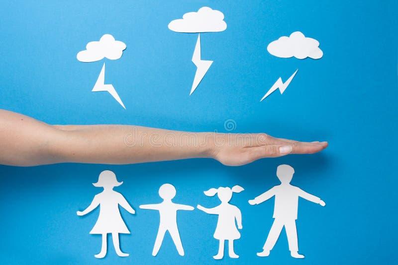 Begrepp av familjsäkerhet Livförsäkring- och familjhälsa Pappers- händer för origamifolkhåll royaltyfri fotografi