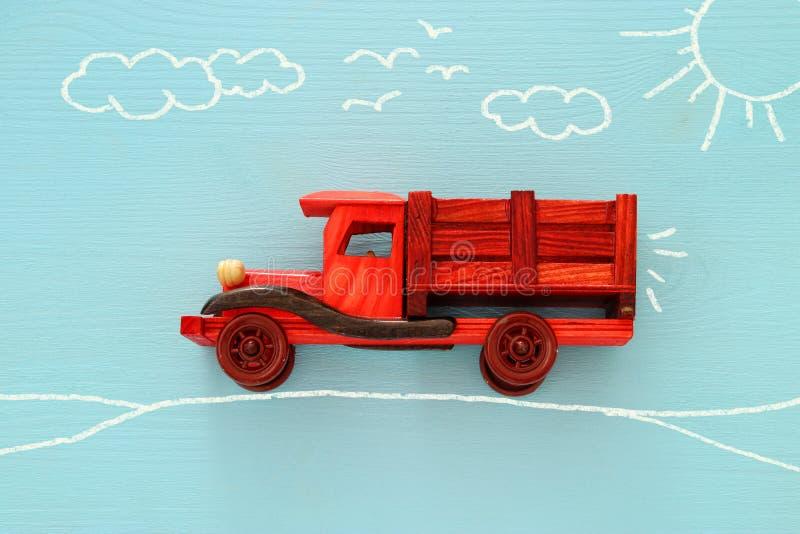 Begrepp av fantasi, kreativitet, att drömma och barndom Den gamla träleksakbilen med informationsdiagram skissar på den blåa bakg arkivfoton