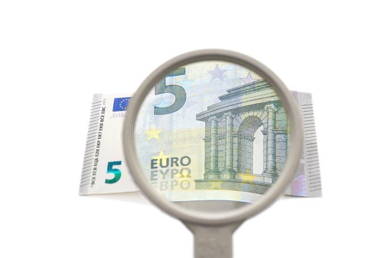 Begrepp av finansiell utredning med förstoringsapparaten och pengar royaltyfri bild
