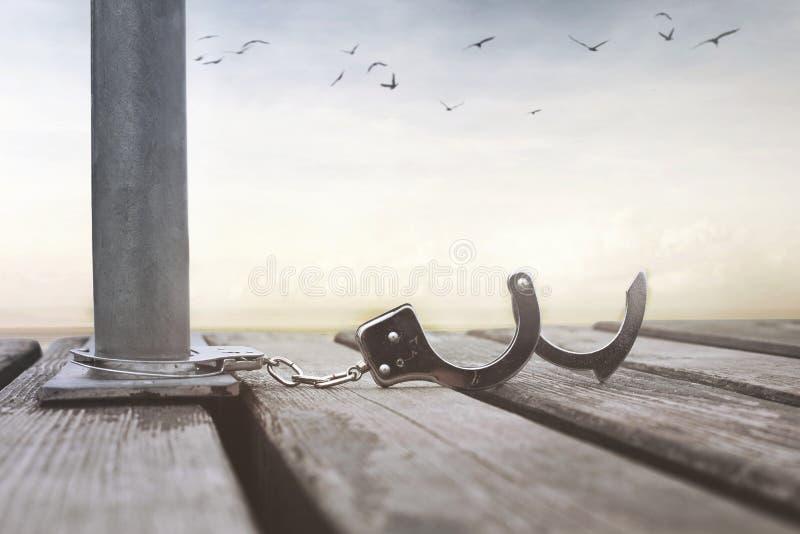 Begrepp av frihet med ett par av öppna handbojor royaltyfri fotografi