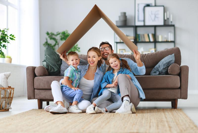 Begrepp av hus och förflyttning lycklig familjmoderfader och ungar med taket hemma royaltyfri fotografi