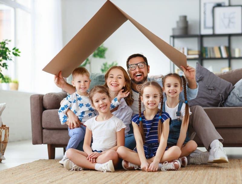 Begrepp av hus och förflyttning lycklig stor familjmoderfader och ungar med taket hemma royaltyfri bild