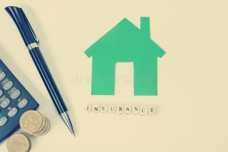 Begrepp av husköpet och försäkring Tabell för kontorsskrivbord med bästa sikt för tillförsel Räknemaskin guld- mynt, penna arkivbilder