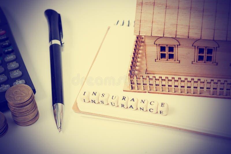 Begrepp av husköpet och försäkring Tabell för kontorsskrivbord med bästa sikt för tillförsel Räknemaskin guld- mynt, penna arkivfoton