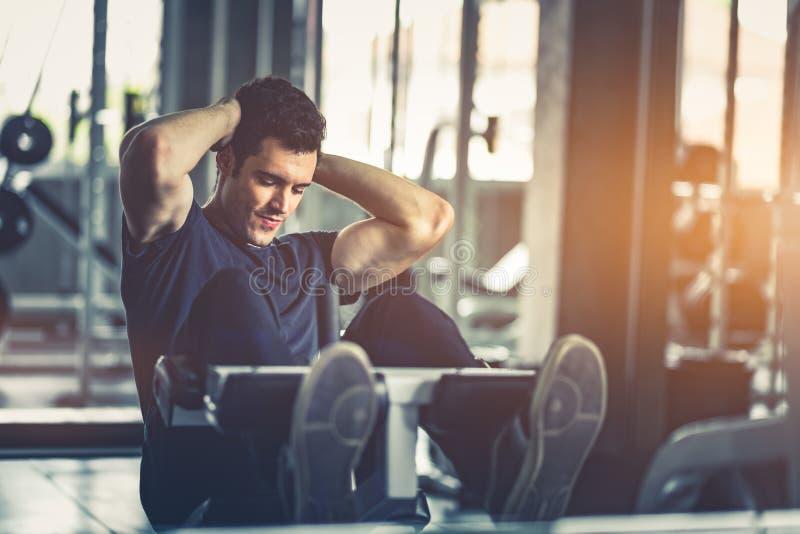 Begrepp av idrottshallen, kondition, sport som är sund, livsstil Den färdiga unga mannen sitter ups på maskinen i sportswear arkivbilder
