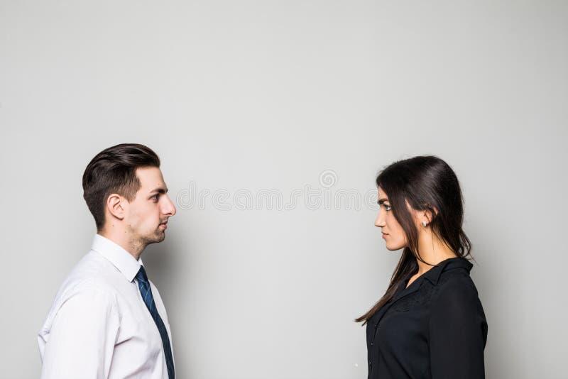Begrepp av konfrontation i affär Stäng sig upp fotoet av två unga allvarliga säkra personer som ansikte mot ansikte till varandra royaltyfri fotografi