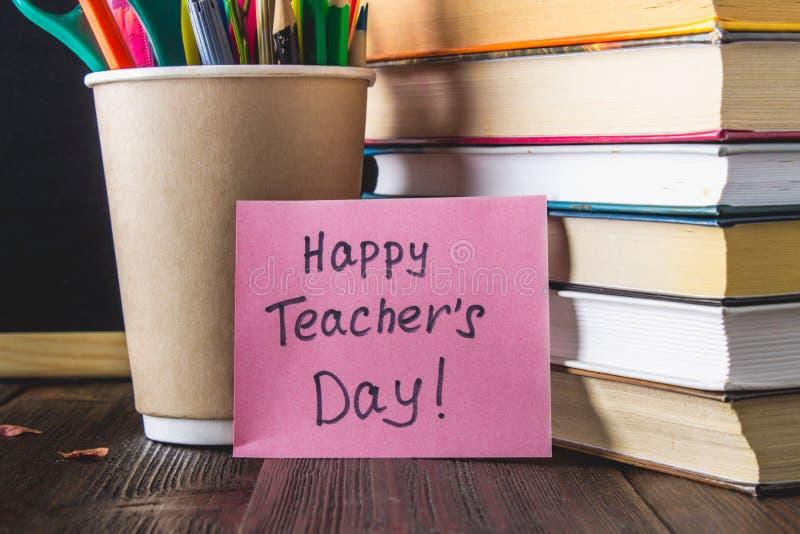 Begrepp av lärares dag Objekt på en svart tavlabakgrund Böcker grönt äpple, platta: Lyckliga lärares dag, blyertspennor och penno royaltyfri foto