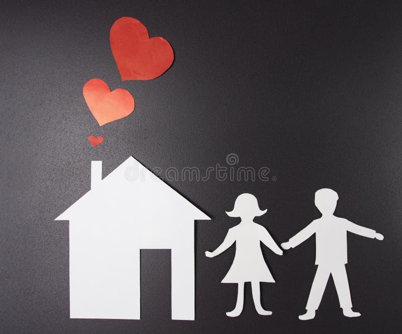 Begrepp av lycka, familjen och hemmet Förälskelse i familj Hus och konturer av män och kvinnor av papper på svart bakgrund arkivbilder