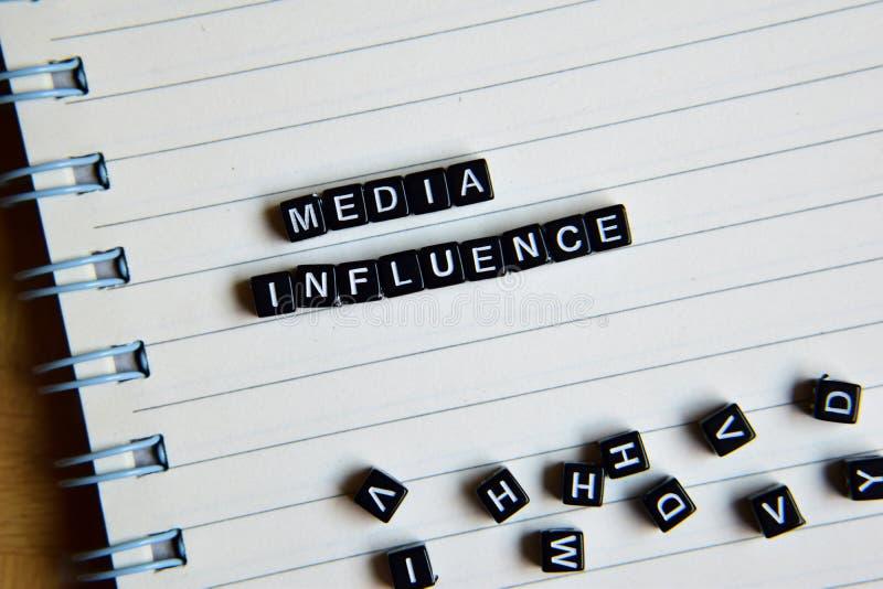 Begrepp av massmediapåverkan på träkuber med böcker i bakgrund arkivbild