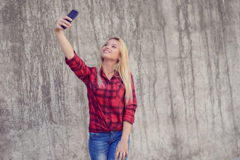 Begrepp av modern teknologi i modernt liv Ung lycklig flicka som tar phoyoen för danandesjälvselfie som fotograferar bilden på mo arkivfoton