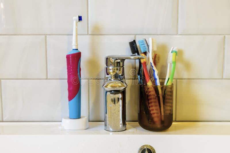 begrepp av muntlig hygien av en stor familj m?nga olika tandborstar p? bakgrunden av vattenkranen och vasken arkivbilder