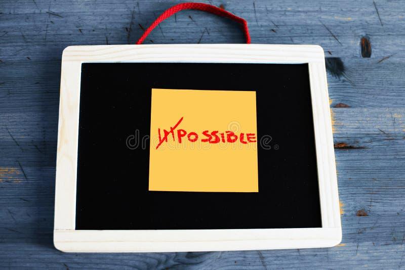 Begrepp av omöjligt att blir möjligt skriftligt på svarten royaltyfri bild