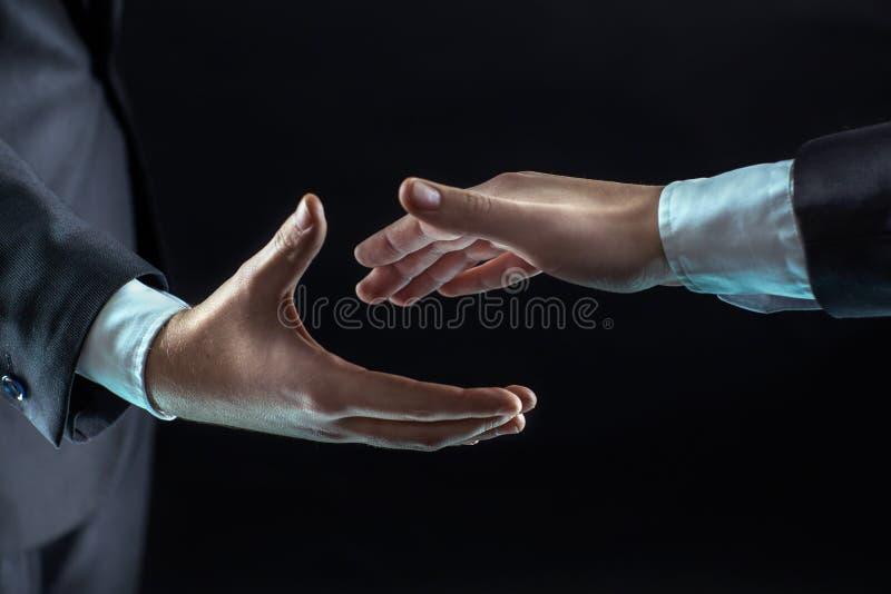 Begrepp av partnerskap i affär: två affärsmanelasticiteter hans hand framåtriktat för en handskakning royaltyfri bild
