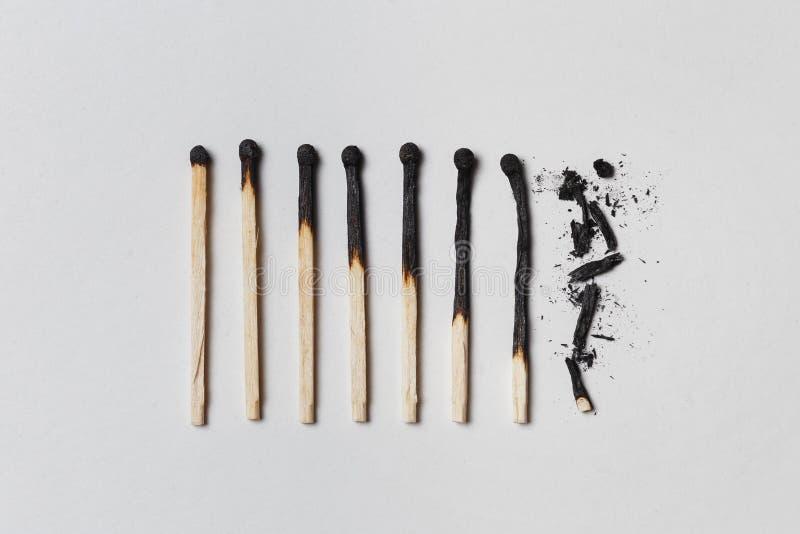 Begrepp av patiens En rad av brända matcher, från från vänster till höger, från nästan en hel match till en fullständigt bränd ma arkivfoton