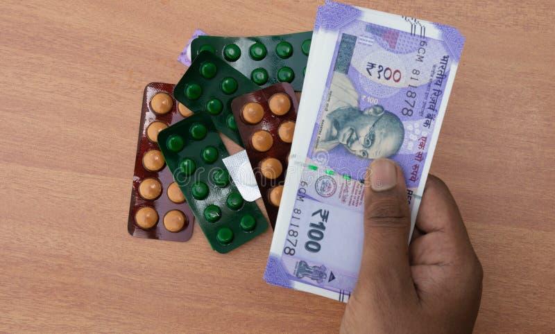 Begrepp av personens händer som köper piller eller minnestavlor med indisk valuta arkivbilder