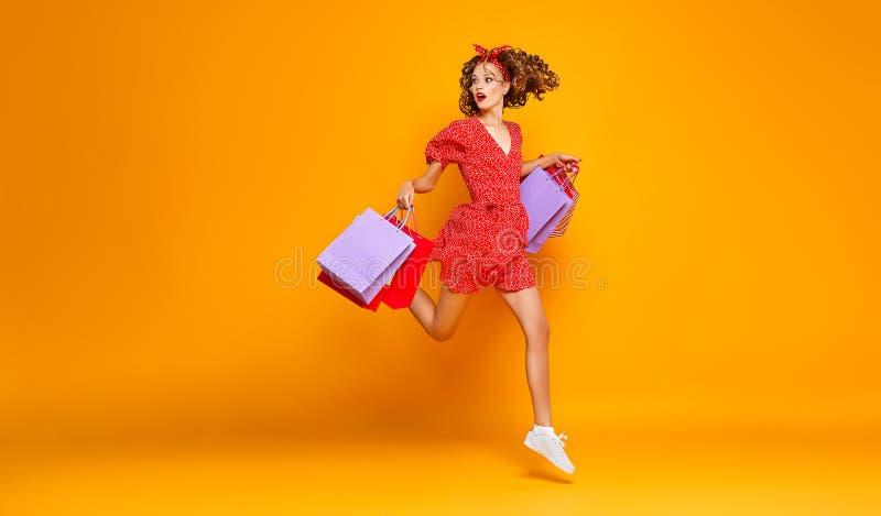 Begrepp av shoppingk?p och f?rs?ljningar av den lyckliga unga flickan med packar p? gul bakgrund royaltyfri bild
