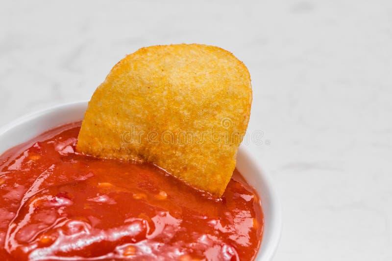 Begrepp av sjuklig mat Lökpotatischiper med varm chili sa arkivfoto