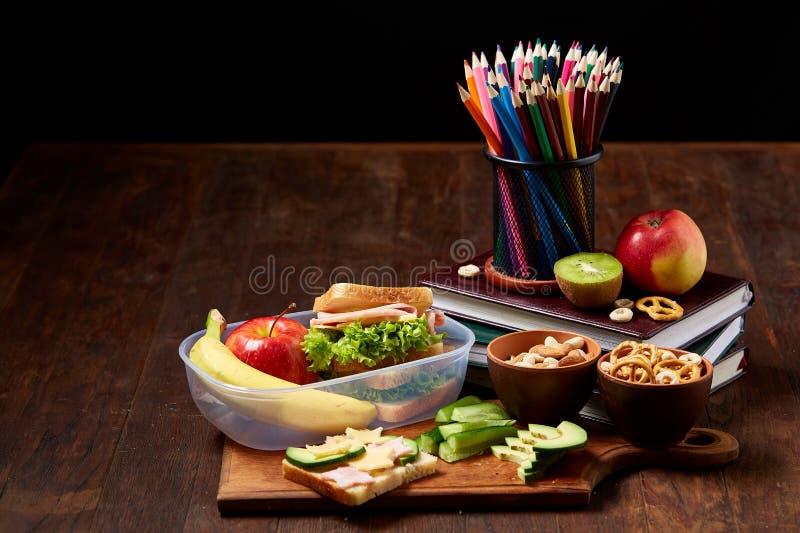 Begrepp av skolalunchavbrottet med den sunda lunchasken och skolatillförsel på träskrivbordet, selektiv fokus royaltyfri fotografi
