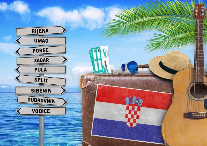 Begrepp av sommarresanden med den gammal resväskan och Kroatien royaltyfri foto