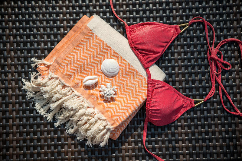 Begrepp av sommartillbehörnärbilden av den orange och vita turkiska handduken, bikiniöverkanten och vitsnäckskal på rottingdagdri arkivbild