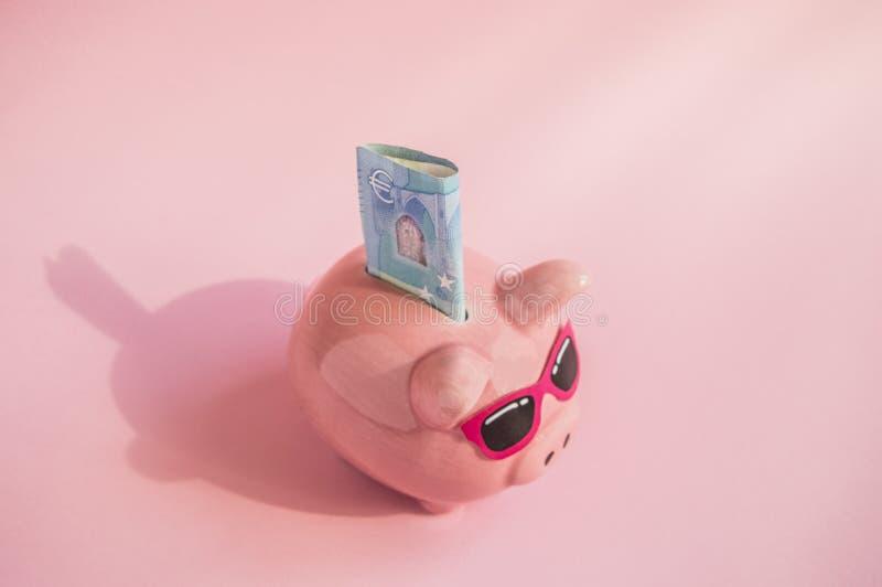 Begrepp av sparande pengar p? din tur- eller semestersvinspargris med solglas?gon p? r?kningen av euro p? en rosa bakgrund, st?ll royaltyfri bild