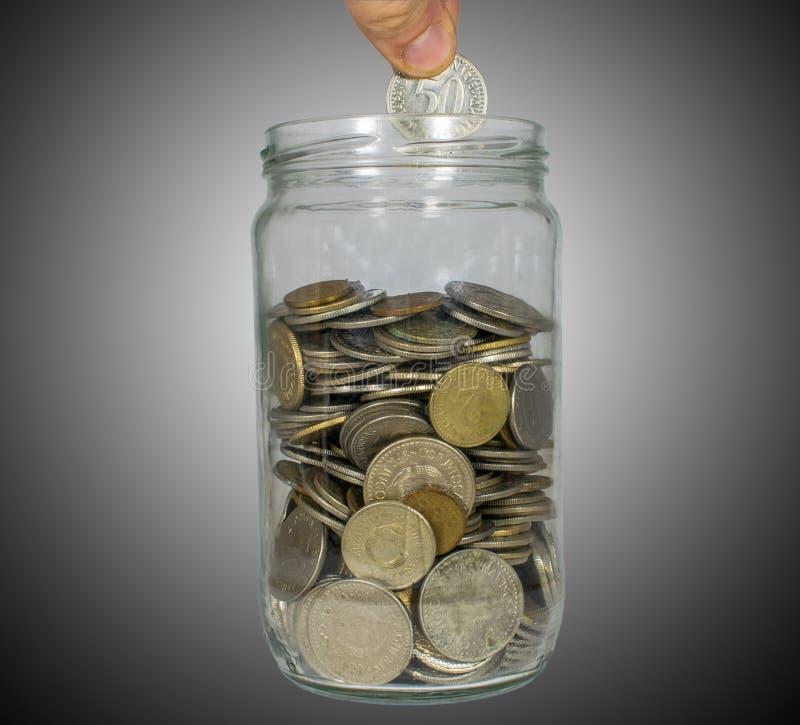 Begrepp av sparande pengar som sätter pengar in i pengarkruset, förhöjningbesparingar royaltyfri foto